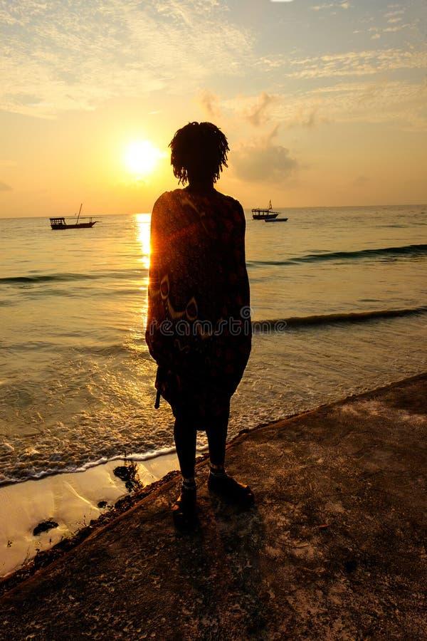 Masai männliche Silhouette am Strand von Uroa Bay Sansibar bei Sonnenaufgang lizenzfreies stockbild