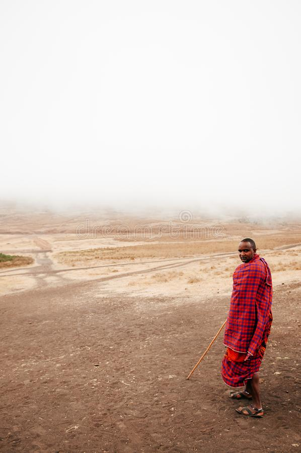 Masai or Maasai tribe man in red cloth in empty golden dusty land. Ngorongoro Consevation, Serengeti Savanna forest in Tanzania royalty free stock image