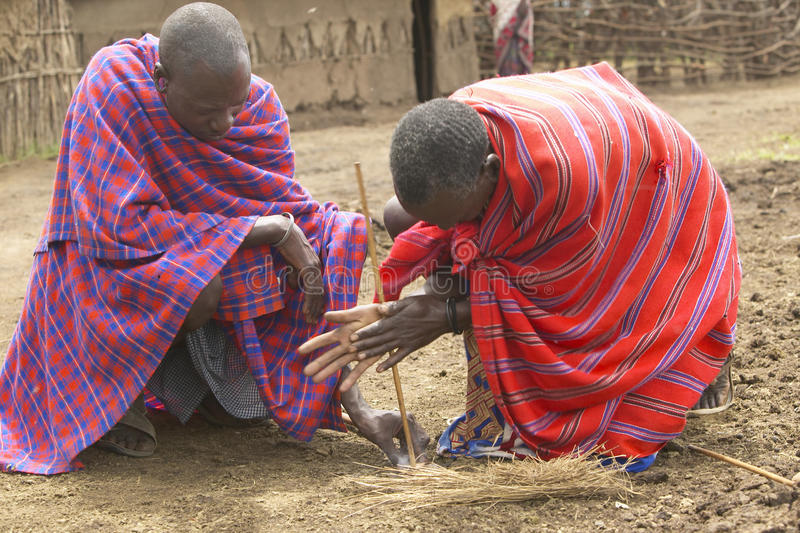 Masai male making fire by rubbing sticks together in village near Tsavo National Park, Kenya, Africa royalty free stock photo