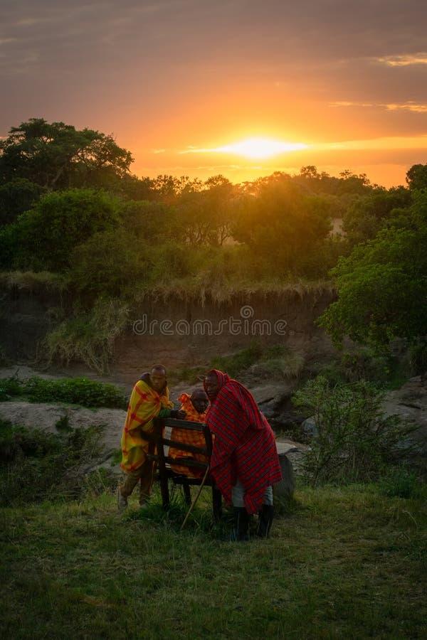 Masai Mara, Кения, Африка – 10-ое августа 2018: Группа в составе люди Masai в традиционных одеждах отдыхая на зоре после длинной  стоковая фотография