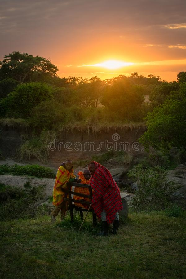 Masai Mara, Kenya, Africa – August 10, 2018: A group of Masai men in traditional clothes resting at dawn after a long night stock photography