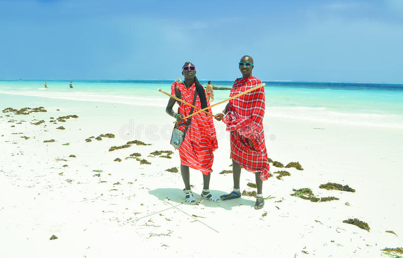 Masai men on the beach. Zanzibar, Kiwengwa - 15 January, 2015: two young masai men in their original red clothes stood still for a moment, on the local beach of stock image