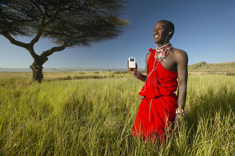 Masai Warrior near Acacia Tree listening to music on iPod by Apple in red surveying landscape of Lewa Conservancy, Kenya Africa royalty free stock photo
