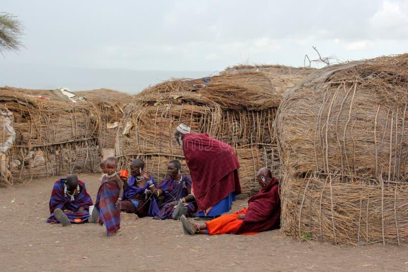 Masaidorfbewohner, die außerhalb ihrer Strohhütten sprechen lizenzfreie stockfotografie