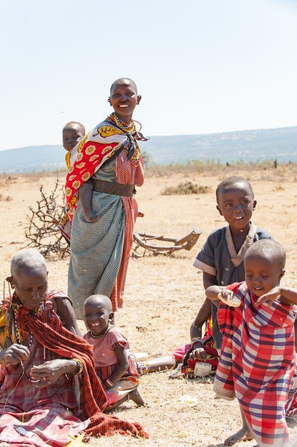 Masaimensen, Vrouwen en Kinderen van Maasai-Stamzitting op grond, Tanzania, Afrika stock afbeelding