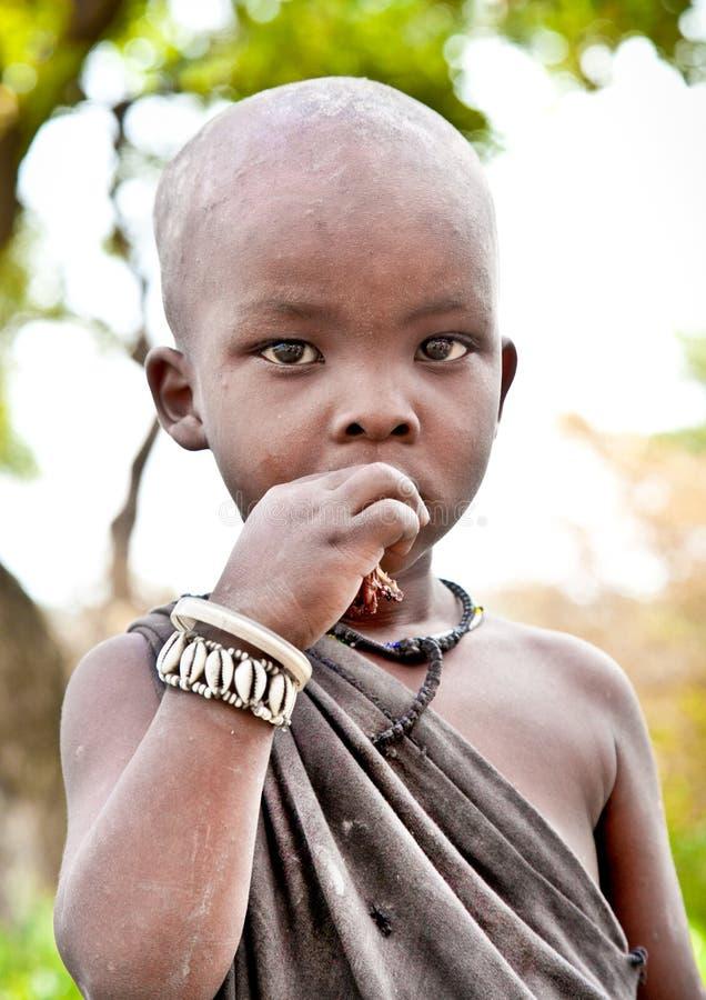 Masaistampojke som ser till kameran i Tanzania arkivfoton