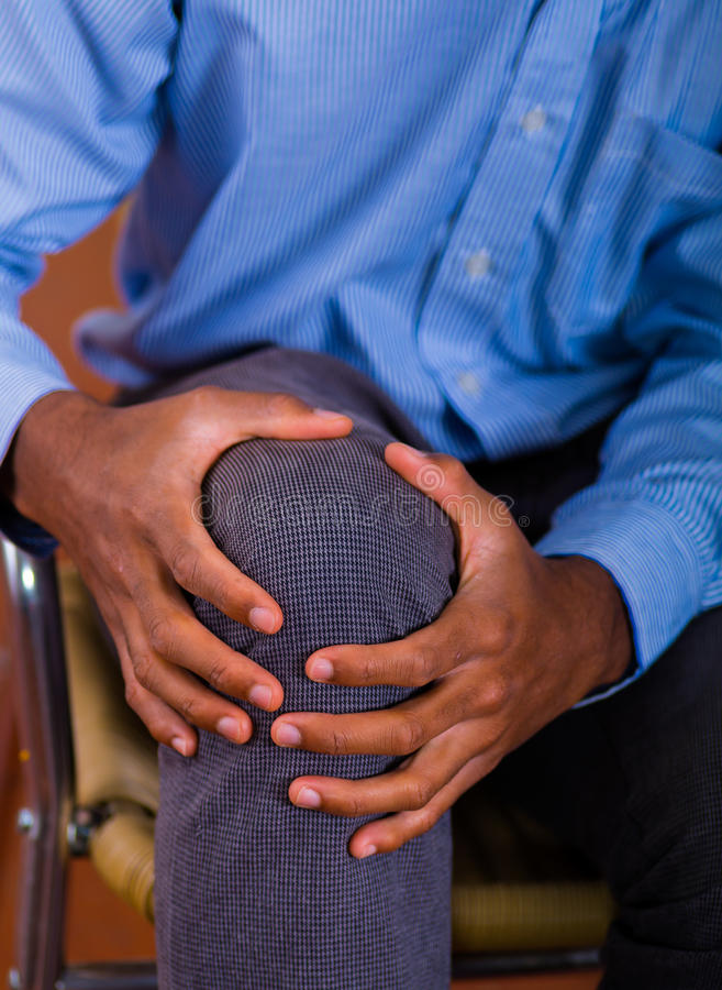 Masaje cuando viene el dolor, ayuda de la rodilla de ambas manos foto de archivo libre de regalías