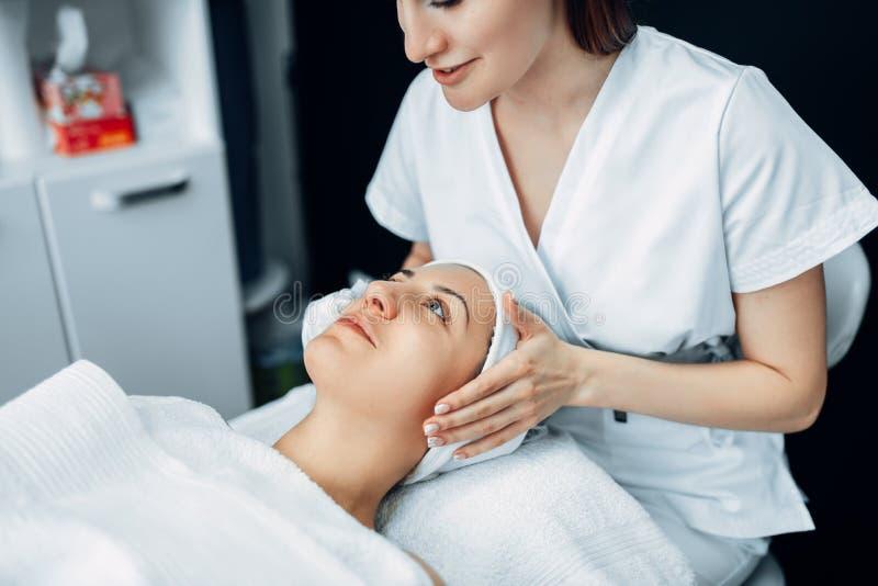 Masaje de cara al paciente femenino, clínica de la cosmetología fotos de archivo