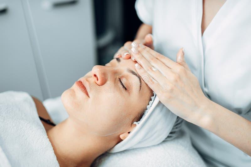 Masaje de cara al paciente femenino, clínica de la cosmetología foto de archivo libre de regalías