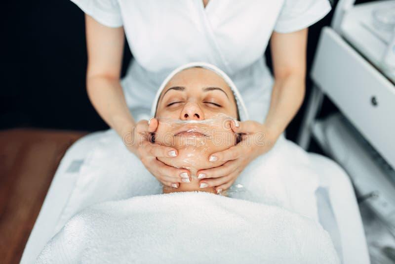 Masaje de cara al paciente femenino, clínica de la cosmetología imagen de archivo libre de regalías
