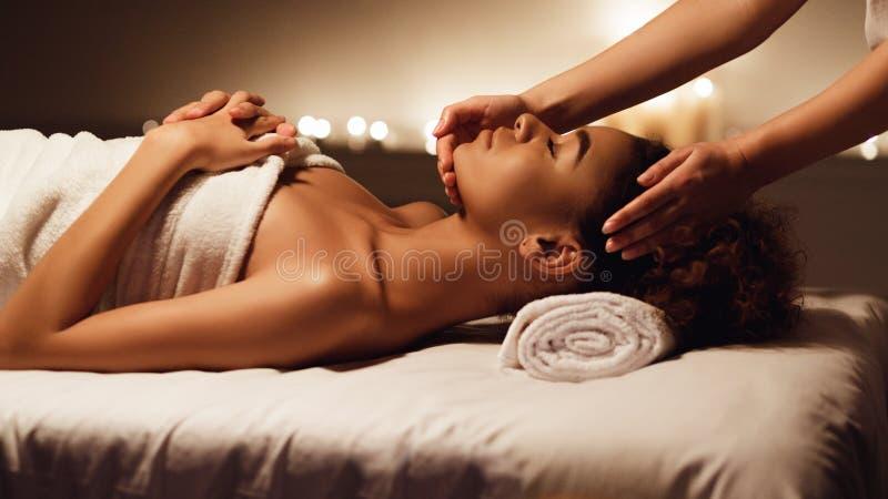 Masaje de cara Mujer afroamericana que consigue el tratamiento del balneario foto de archivo