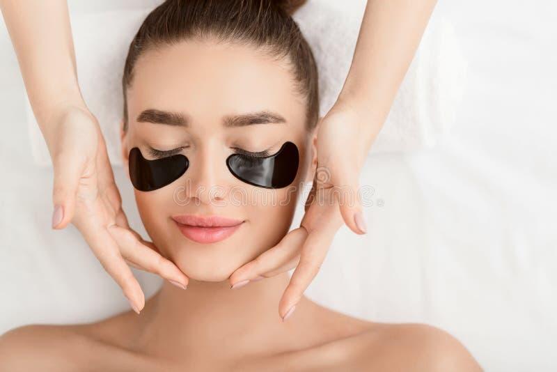 Masaje de cara Mujer con los remiendos del ojo morado imagen de archivo