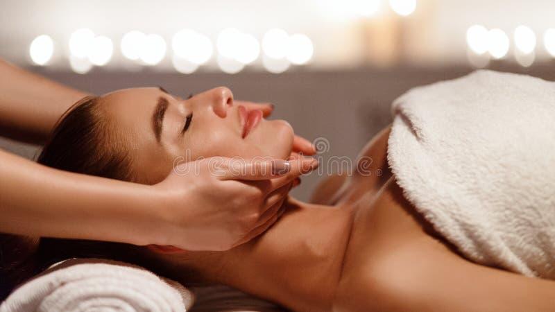Masaje de cara Mujer joven que consigue el tratamiento del balneario imagen de archivo