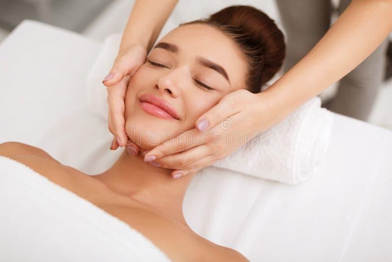 Masaje de cara Mujer que consigue el tratamiento del balneario en salón fotos de archivo