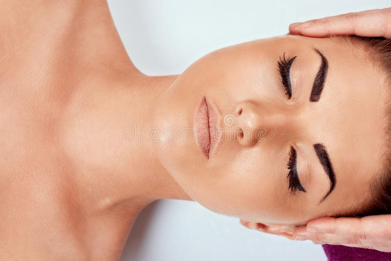 Masaje de cara Primer de la mujer joven que consigue el tratamiento del masaje del balneario en el sal?n del balneario de la bell fotos de archivo
