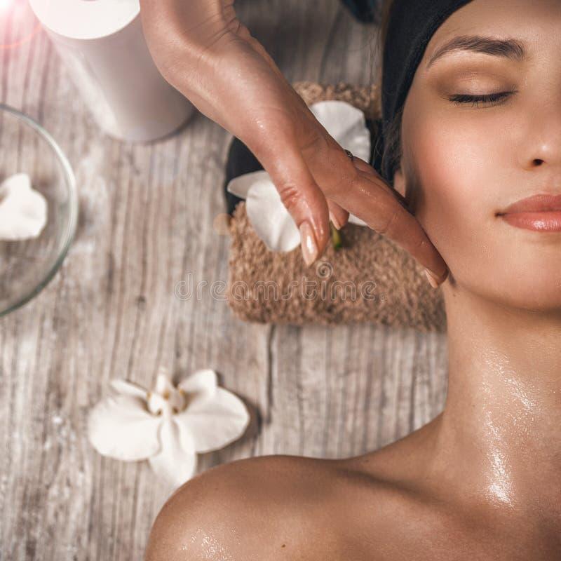 Masaje de cara Spa Salón de la belleza Retrato de una mujer sonriente joven hermosa Foto del primer fotografía de archivo libre de regalías