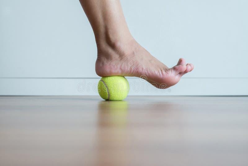 Masaje de la mujer con la pelota de tenis a su pie en dormitorio, pies de lenguados o el masaje del talón para el fasciitis plant imagen de archivo libre de regalías