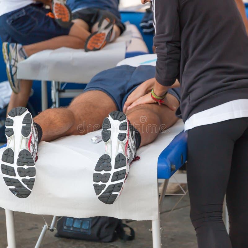 Masaje de la relajación de los atletas antes del acontecimiento deportivo fotografía de archivo