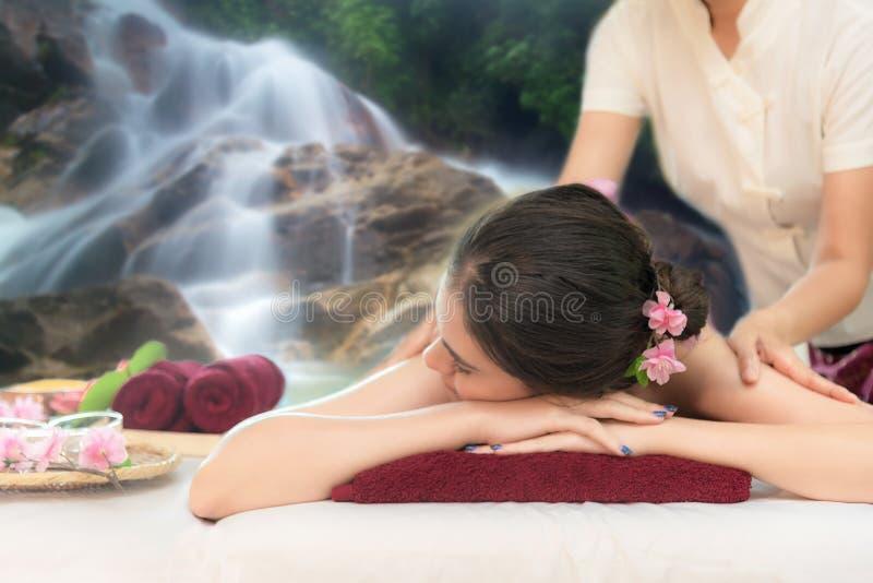 Masaje de la savia en naturaleza de la cascada El masajista que hace masaje con el azúcar del tratamiento friega en cuerpo asiáti foto de archivo