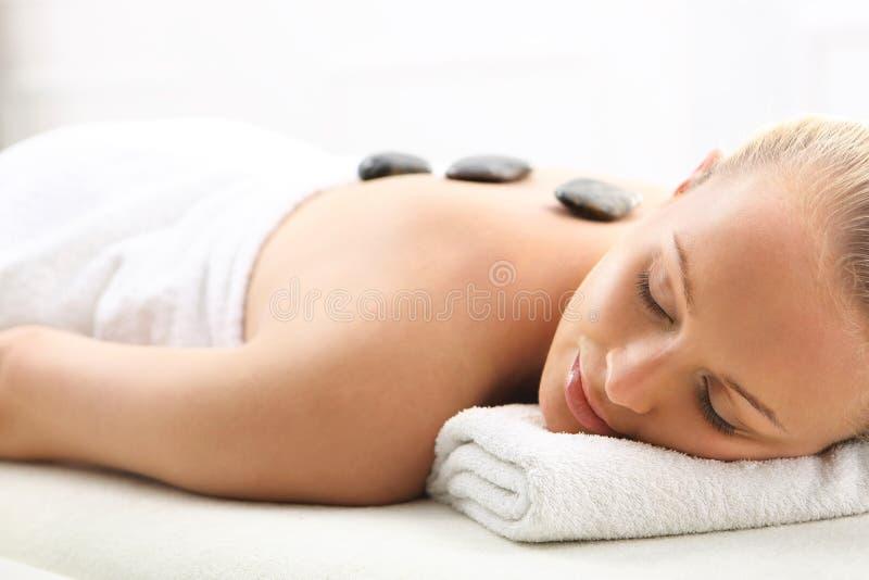 Masaje de piedra caliente, mujer en salón del balneario imagen de archivo