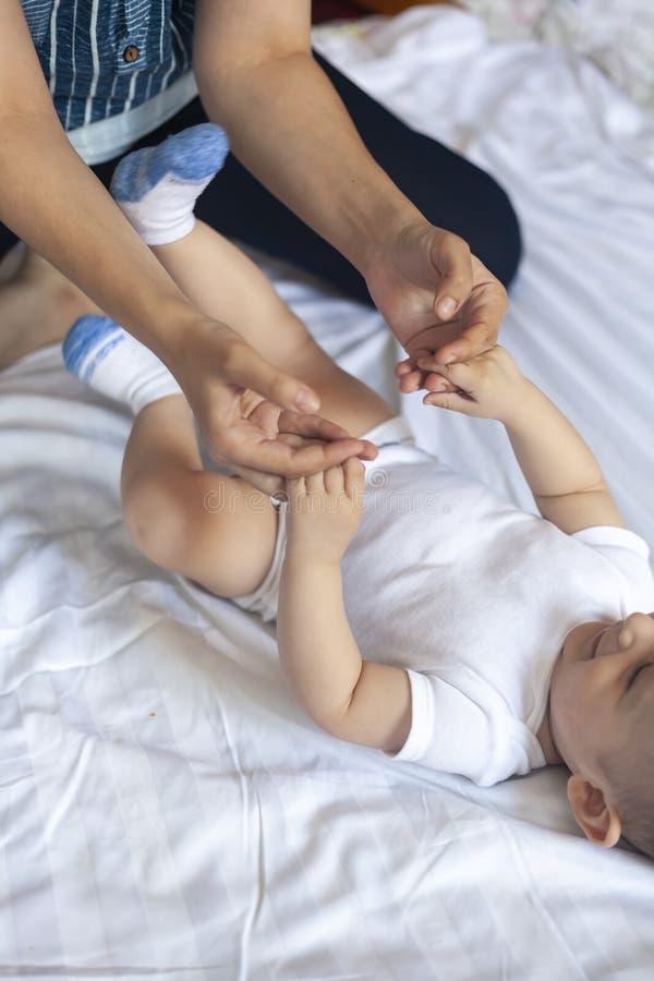 Masaje del beb? Mam? que hace la gimnasia con el ni?o foto de archivo libre de regalías