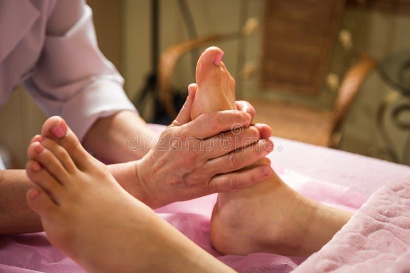 Masaje del pie en el salón del balneario, primer, mujer joven que tiene massa de los pies imagenes de archivo