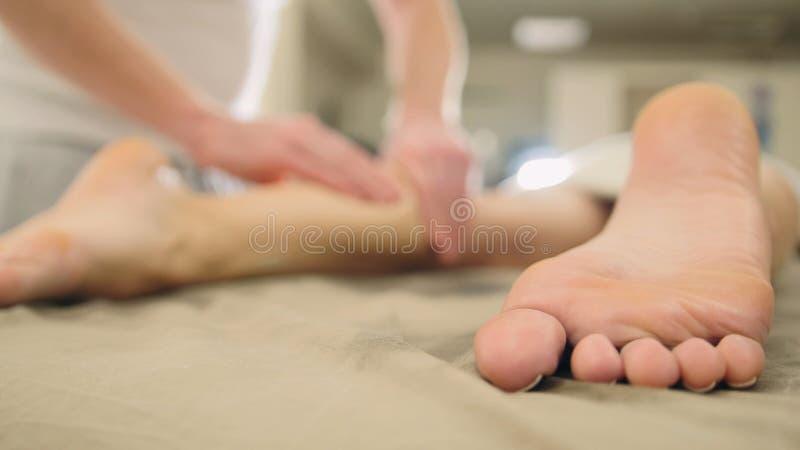 Masaje para el pie y las piernas en salón del balneario - terapia de relajación, cosmético y concepto de la atención sanitaria imagenes de archivo