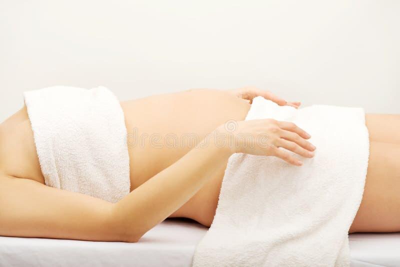 Masaje relajante que espera de la mujer embarazada para imagen de archivo