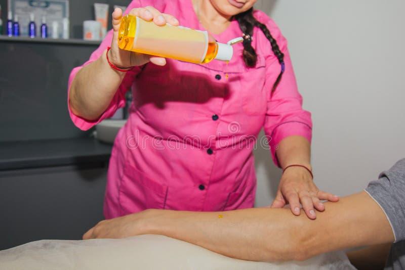 Masaje terapéutico profesional de la mano usando el aceite del masaje el doctor de la mujer da masajes a un atleta del hombre en  imagen de archivo libre de regalías