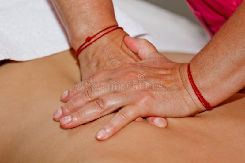 Masaje terapéutico profesional de la parte posterior y del cuello el doctor de la mujer da masajes al atleta de la muchacha en un imágenes de archivo libres de regalías