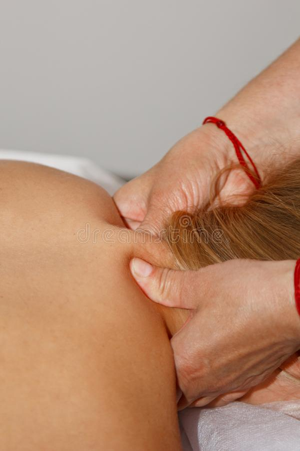 Masaje terapéutico profesional de la parte posterior y del cuello el doctor de la mujer da masajes al atleta de la muchacha en un imagen de archivo