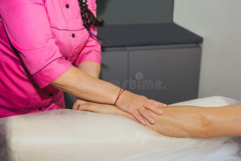Masaje terapéutico profesional de las manos y de las palmas el doctor de la mujer da masajes a un atleta del hombre en un cuarto  imagen de archivo