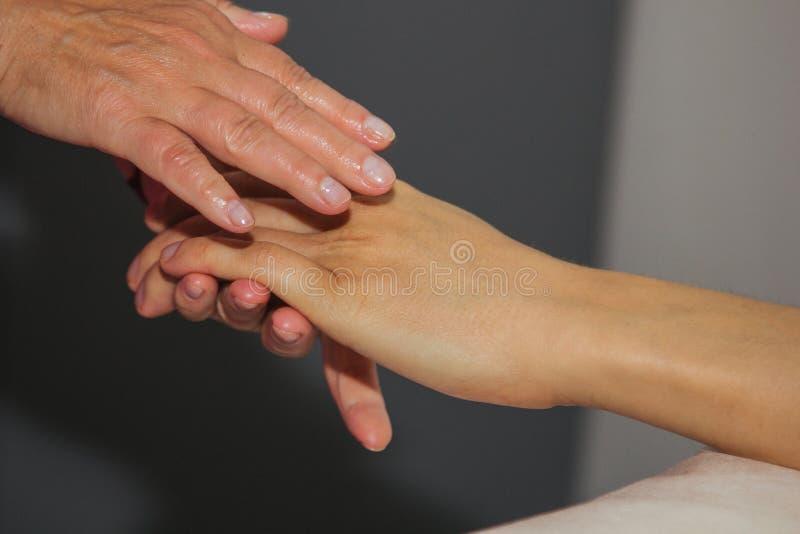 Masaje terapéutico profesional de las manos y de las palmas el doctor de la mujer da masajes a un atleta del hombre en un cuarto  fotografía de archivo libre de regalías