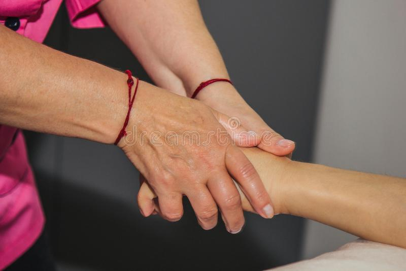 Masaje terapéutico profesional de las manos y de las palmas el doctor de la mujer da masajes a un atleta del hombre en un cuarto  imagenes de archivo