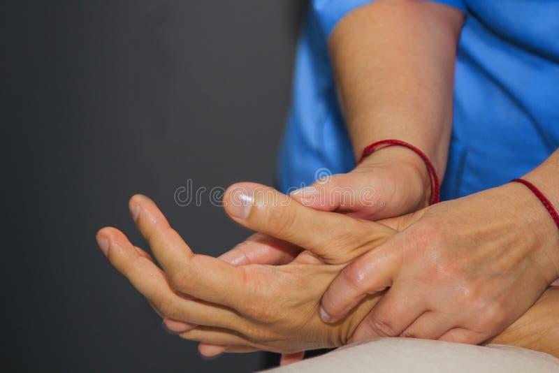 Masaje terapéutico profesional de las manos y de las palmas el doctor de la mujer da masajes a un atleta del hombre en un cuarto  fotos de archivo