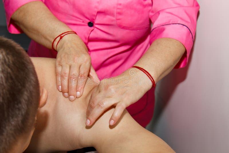 Masaje terapéutico profesional del hombro y del cuello el doctor de la mujer da masajes a un atleta del hombre en un cuarto del m imagen de archivo libre de regalías
