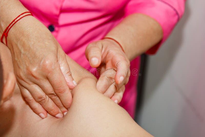 Masaje terapéutico profesional del hombro y del cuello el doctor de la mujer da masajes a un atleta del hombre en un cuarto del m fotos de archivo libres de regalías