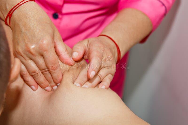 Masaje terapéutico profesional del hombro y del cuello el doctor de la mujer da masajes a un atleta del hombre en un cuarto del m foto de archivo libre de regalías