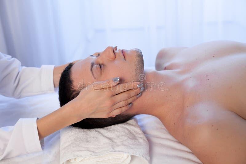 Masajista de sexo masculino que hace el masaje del balneario de la terapia de la cara y del cuello fotografía de archivo libre de regalías