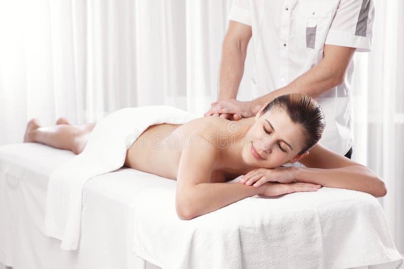 Masajista profesional que hace el masaje de la parte posterior de la hembra imagenes de archivo