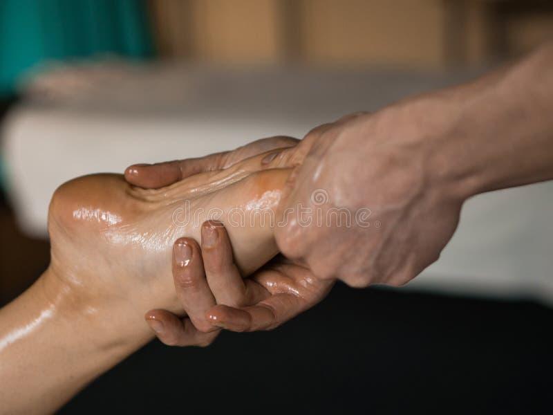 Masajista profesional que hace masaje engrasado tejido profundo a una muchacha en la sesión del masaje de Ayurveda imagenes de archivo