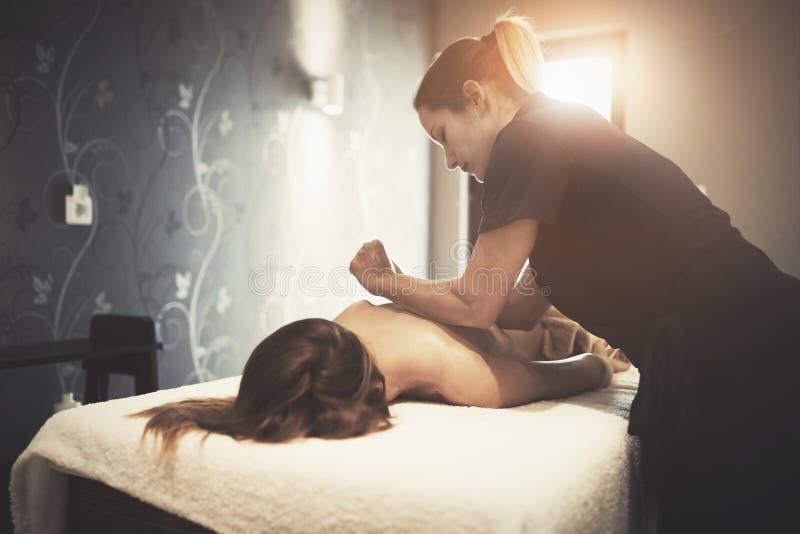 Masajista que da masajes al cliente femenino en el centro turístico fotos de archivo