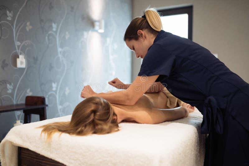 Masajista que da masajes detrás de hembra fotos de archivo libres de regalías