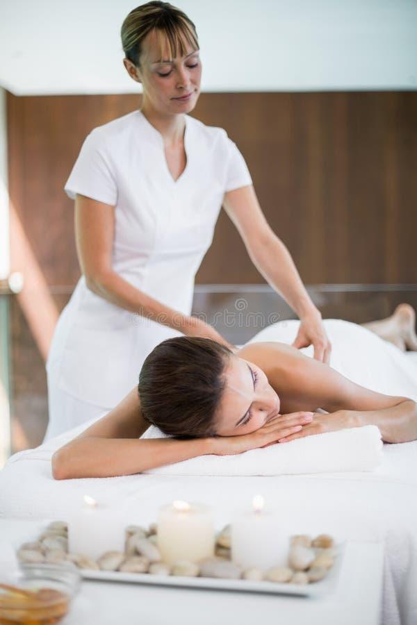 Masajista que da masajes detrás de mujer fotos de archivo libres de regalías
