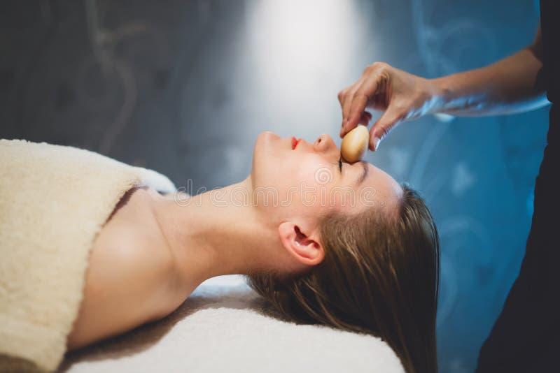 Masajista que da masajes a la cara con los objetos calentados imagenes de archivo