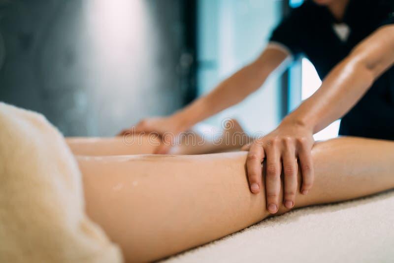 Masajista que da masajes a la masajista durante el tretment terapéutico fotos de archivo