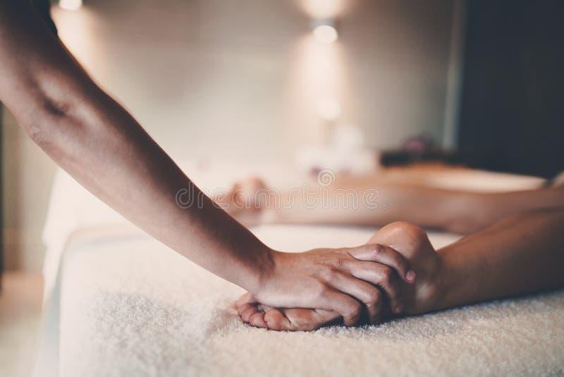 Masajista que da masajes a la masajista durante el tretment terapéutico imagenes de archivo