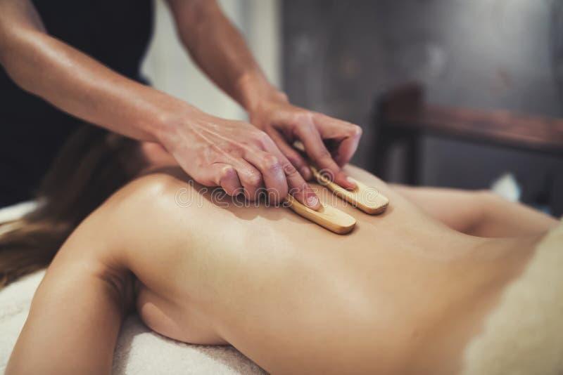 Masajista que da masajes a la hembra en cama fotos de archivo