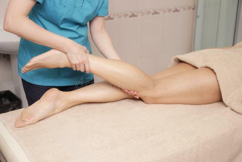Masajista que hace el masaje terapéutico del pie para una mujer fotos de archivo