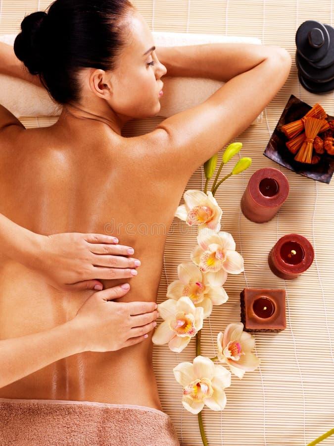 Masajista que hace masaje en la parte posterior de la mujer en salón del balneario imagen de archivo libre de regalías